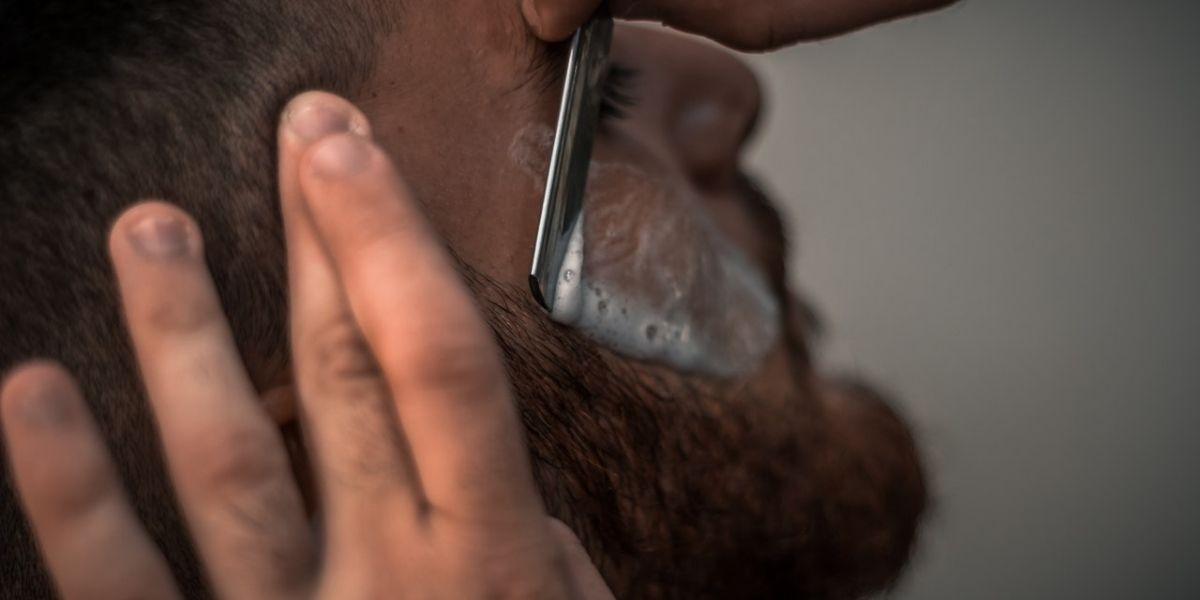 man with red beard getting a straight razor shave