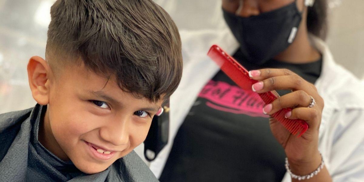 little boy smiling while getting a hair cut