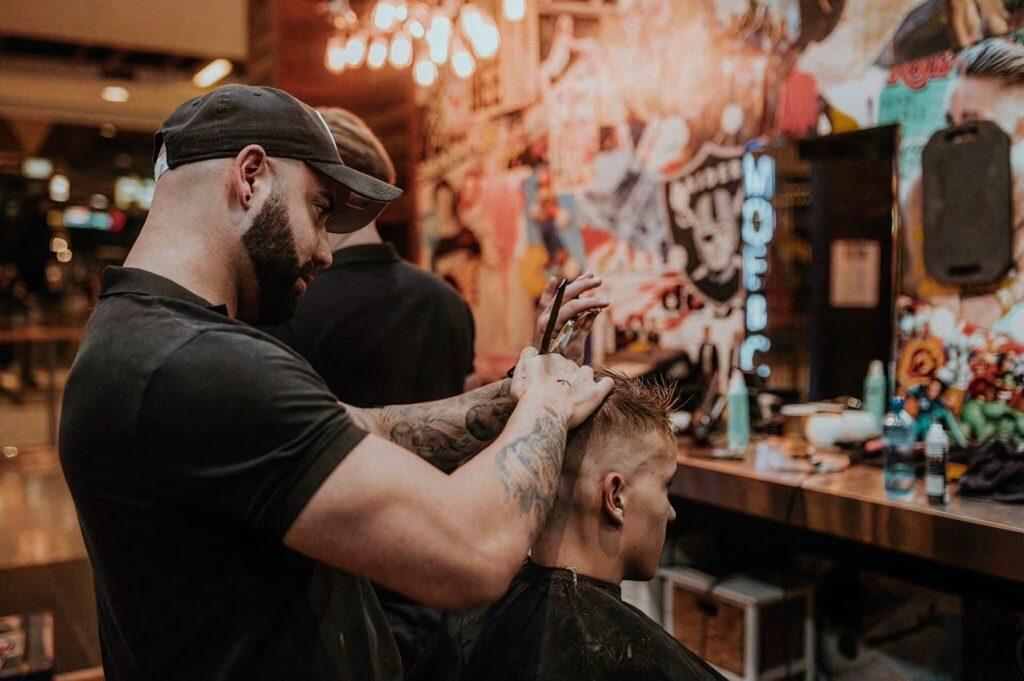 man getting a hair cut from a barber